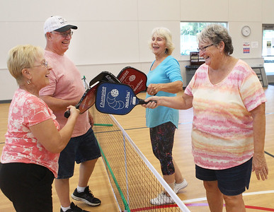 Candace H. Johnson-For Shaw Media Darlene and Bob Fenrich, of Fox Lake greet Ruth Collins, of Bristol, Wis., and Marcia Wolf, of Ingleside up at the net after their game of pickleball at Lakefront Park in Fox Lake. Pickleball is offered Monday & Wednesday 1-4:30 pm and Thursday 6-7:30 pm at Lakefront Park.(7/2/18)