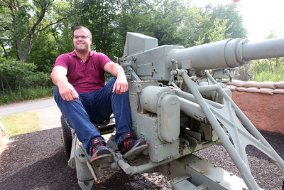 Candace H. Johnson-For Shaw Media Kevin Tajer, of Arlington Heights sits on a utility vehicle holding a Bofors 40mm automatic gun which represents the Fort Sheridan military history on display at the Fort Sheridan Forest Preserve.Tajer is an Army veteran.(7/9/18)