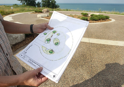 Candace H. Johnson-For Shaw Media Michael Haug, of Libertyville, landscape architect and construction project manager, with the Lake County Forest Preserves holds the landscape plan he designed and drafted for the Lake Overlook at the Fort Sheridan Forest Preserve.(7/9/18)
