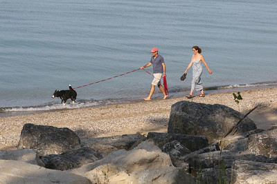 Candace H. Johnson-For Shaw Media Scott Schappe and his wife, Tracy McCabe, of Lake Forest take a walk with their dog, Nike, along the lakefront at the Fort Sheridan Forest Preserve.(7/9/18)