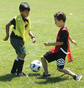 Candace H. Johnson-For Shaw Media Jayden Salinas, 8, and Karl Knopfhart, 6, both of Gurnee battle for control in a game during the Chicago Fire Soccer Camp at Viking Park in Gurnee. The camp was sponsored by the Gurnee Park District.(7/10/18)