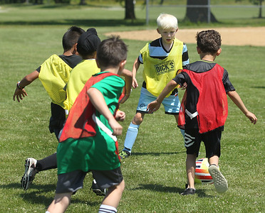 Candace H. Johnson-For Shaw Media Oliver Gross, 9, (second from right) looks to defend as Karl Knopfhart, 6, both of Gurnee takes control of the ball in their game during the Chicago Fire Soccer Camp at Viking Park in Gurnee. The camp was sponsored by the Gurnee Park District.(7/10/18)