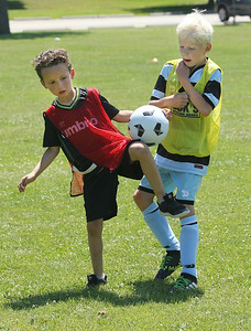 Candace H. Johnson-For Shaw Media Karl Knopfhart, 6, and Oliver Gross, 9, both of Gurnee try and stop the ball as they battle for control while they play their game during the Chicago Fire Soccer Camp at Viking Park in Gurnee. The camp was sponsored by the Gurnee Park District.(7/10/18)