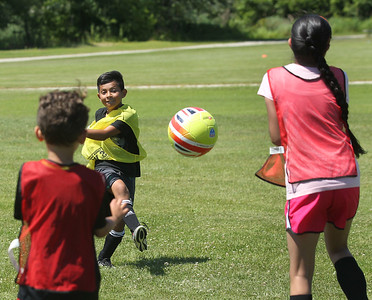 Candace H. Johnson-For Shaw Media Jayden Salinas, 8, (center) aims for the goal as Karl Knopfhart, 6, both of Gurnee and Pawanpreet Kaur, 9, of Waukegan defend in a game during the Chicago Fire Soccer Camp at Viking Park in Gurnee. The camp was sponsored by the Gurnee Park District.(7/10/18)