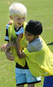Candace H. Johnson-For Shaw Media Oliver Gross, 9, of Gurnee and Jujhar Singh, 6, of Waukegan celebrate their team's goal while they play a game during the Chicago Fire Soccer Camp at Viking Park in Gurnee. The camp was sponsored by the Gurnee Park District.(7/10/18)