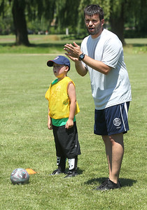 Candace H. Johnson-For Shaw Media Noah Fletcher, 7, of Gurnee stands next to his coach, Fernando Martinez, of Gurnee during drills for the Chicago Fire Soccer Camp at Viking Park in Gurnee. The camp was sponsored by the Gurnee Park District.Coach Martinez just came to Gurnee from Spain.(7/10/18)