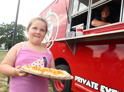 Candace H. Johnson-For Shaw Media Josie Bowman, 7, of Spring Grove gets some buffalo chicken pizza from Tammy Hinchee, of Woodstock with Your Sister's Tomato wood fired pizza at the Fox Lake Farmers Market at the Community Garden Green on 17 E. School Court in Fox Lake. The farmers market runs on Tuesdays from 4-8 pm. (7/10/18)