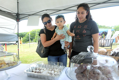 Candace H. Johnson-For Shaw Media Sylvia Velazquez, of Fox Lake and her daughters, Arisbeth, nine-months-old, and Alexa, 15, look to buy  homemade baked goods from Carly's Kolaches at the Fox Lake Farmers Market at the Community Garden Green on 17 E. School Court in Fox Lake. The farmers market runs on Tuesdays from 4-8 pm. (7/10/18)