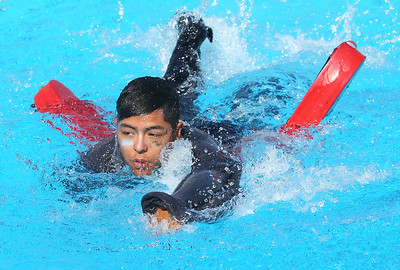 Candace H. Johnson-For Shaw Media Gurnee Park District's Eric Salgado, 18, of Wadsworth competes in the Lifeguard Challenge Relay fully clothed as he swims with a lifeguard tube during the Lifeguard Games at the Hunt Club Park Aquatic Center in Gurnee. The Gurnee Park District hosted the event.(7/11/18)