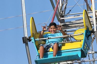 Candace H. Johnson-For Shaw Media Samuel Ayala, 12, of Round Lake Beach waves to his mother, Berenise, as he rides the Ferris Wheel during BeachFest at the Cultural & Civic Center in Round Lake Beach.(7/14/18)