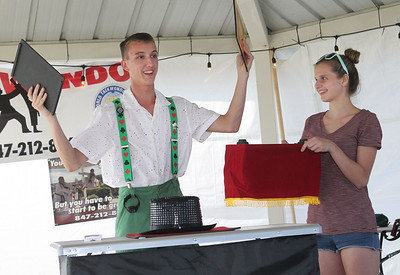 Candace H. Johnson-For Shaw Media Magician Dynamic Dylan gets some help from his girlfriend, Allison Morris, both 18, of Antioch as he does his Presto the Elephant magic trick during BeachFest at the Cultural & Civic Center in Round Lake Beach.(7/14/18)