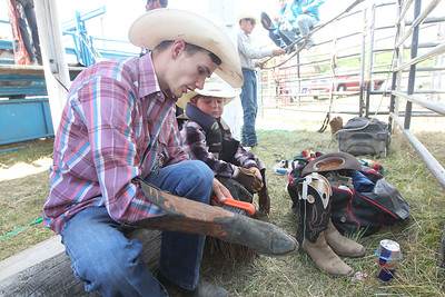 Candace H. Johnson-For Shaw Media Corey Bailey, of Buchanan, Tenn., talks with Wheaton West, 5, of Jasonville, Ind., as he cleans his cowboy boots before competing in the Bull Riding event during the 55th Annual Wauconda Rodeo at the Golden Oaks Equestrian Center in Wauconda.The event was sponsored by the Wauconda Chamber of Commerce. (7/15/18)