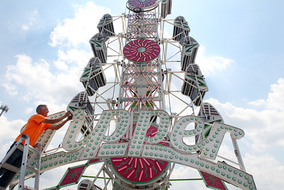 Candace H. Johnson-For Shaw Media Doug Skinner, of Harvard, with Skinner Amusements, fixes some LED lights on the Zipper ride before the start of the Lake County Fair at the Lake County Fairgrounds in Grayslake. The Zipper ride has a couple of thousand lights displayed on it. (7/24/18)