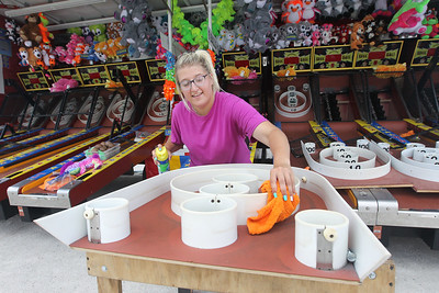 Candace H. Johnson-For Shaw Media Olivia Zimmerman, 21, of Rock City cleans dust off of the Skee Ball game before the start of the Lake County Fair at the Lake County Fairgrounds in Grayslake. (7/24/18)
