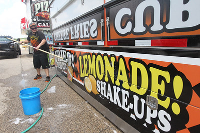 Candace H. Johnson-For Shaw Media Grant Ryals, 21, of Tampa, Fla., cleans the outside of his food trailer before the start of the Lake County Fair at the Lake County Fairgrounds in Grayslake. (7/24/18)
