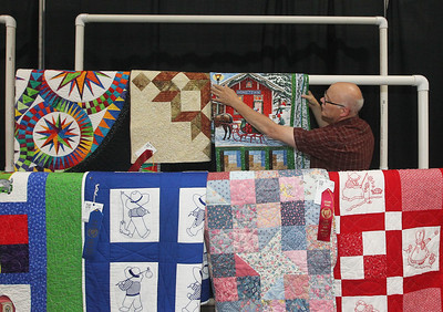 Candace H. Johnson-For Shaw Media Erv Heidemann, of Greenfield, Wis., volunteers to hang up quilts in the Expo Hall before the start of the Lake County Fair at the Lake County Fairgrounds in Grayslake. (7/24/18)
