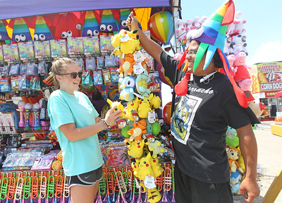 Candace H. Johnson-For Shaw Media Faith Wynn, 17, of Charleston, S.C. and Norberto Santiago, 23, of Orlando, Fla., both with East Coast Concessions set up their toys and novelties stand before the start of the Lake County Fair at the Lake County Fairgrounds in Grayslake. (7/24/18)