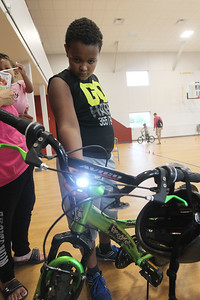 Candace H. Johnson-For Shaw Media Elias Newsome, 10, of Fox Lake checks out the new lights on his bike he received during the Fox Lake Police Bike Rodeo at Lakefront Park in Fox Lake. (7/21/18)