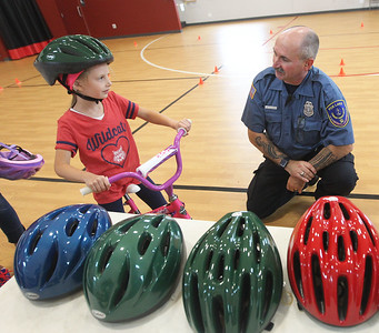 Candace H. Johnson-For Shaw Media Audrey Vasey, 6, of Fox Lake talks with William Fedderly, a Fox Lake community service officer, after he gave her a bicycle helmet to fit over her Cochlear implants during the Fox Lake Police Bike Rodeo at Lakefront Park in Fox Lake.Audrey was at the event with her parents Matt and Dana, and brother, Mason, 10. (7/21/18)