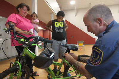 Candace H. Johnson-For Shaw Media Amy Newsome, of Fox Lake holds her daughter, Kaylise, 1, as her son, Elias, 10, gets some new lights put on his bike by William Fedderly, a Fox Lake community service officer, during the Fox Lake Police Bike Rodeo at Lakefront Park in Fox Lake. (7/21/18)