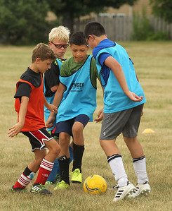 Candace H. Johnson-For Shaw Media Dylan Gates, Kyle Knodell, both 11, Kristian Chadick, 8, and his brother, Paul, 10, all of Lindenhurst battle for control as they play a scrimmage game during the Lindenhurst Park District's TetraBrazil Soccer Camp at Millenium Park in Lindenhurst. (7/19/18)