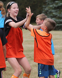 Candace H. Johnson-For Shaw Media Dakota Snow, 13, of Antioch congratulates Dylan Wiedrich, 8, of Lindenhurst on making a goal for their team as they play a scrimmage game during the Lindenhurst Park District's TetraBrazil Soccer Camp at Millenium Park in Lindenhurst. (7/19/18)