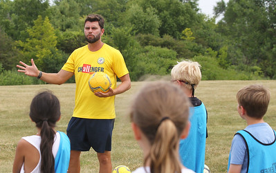 Candace H. Johnson-For Shaw Media Bruno Motta, of Lindenhurst coaches a group of kids during the Lindenhurst Park District's TetraBrazil Soccer Camp as he explains a passing drill at Millenium Park in Lindenhurst. Coach Motta recently came to the United States from Brazil. (7/19/18)