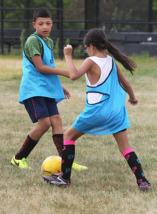 """Candace H. Johnson-For Shaw Media Kristian Chadick, 8, passes the ball to Piper Gibbs, 9, both of Lindenhurst during a passing drill called, """"Keep A Way,"""" during the Lindenhurst Park District's TetraBrazil Soccer Camp at Millenium Park in Lindenhurst. (7/19/18)"""