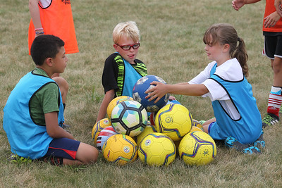 Candace H. Johnson-For Shaw Media Kristian Chadick, 8, and Kyle Knodell, 11, watch Joli Wiedrich, 10, all of Lindenhurst make a soccer ball pyramid as they take a break between the first and second half of their scrimmage game during the Lindenhurst Park District's TetraBrazil Soccer Camp at Millenium Park in Lindenhurst. (7/19/18)