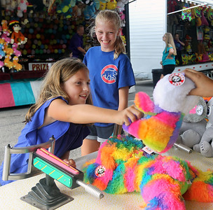 Candace H. Johnson-For Shaw Media McKenna Powers, 9, of Volo reaches for a stuffed animal prize with her sister, Savannah, 12, next to her after she won a Top Glo game during Antioch's Taste of Summer in downtown Antioch. The event was hosted by the Antioch Chamber of Commerce. (7/22/18)