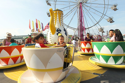 Candace H. Johnson-For Shaw Media Anthony Barnett, of Cary and Scarlett Flathau, of Wonder Lake, both 3, (center) ride the Tea Cups during the 90th Annual Lake County Fair at the Lake County Fairgrounds in Grayslake.