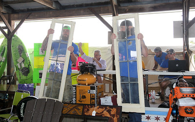 Candace H. Johnson-For Shaw Media Willy Robertson and Mark Lancsak, both of Antioch hold up glass doors for bidders to see at the auction during the Antioch Lions Club Chicken BBQ, Pig Roast & Auction at Williams Park in Antioch.(7/29/18)