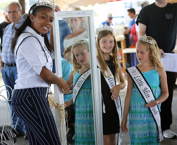 Candace H. Johnson-For Shaw Media Antioch 2018 Queens Alexa Waheed, 17, Bella Dusek, 11, and Ellie Savers, 7, hold up a mirror for bidders to see at the auction during the Antioch Lions Club Chicken BBQ, Pig Roast & Auction at Williams Park in Antioch.(7/29/18)