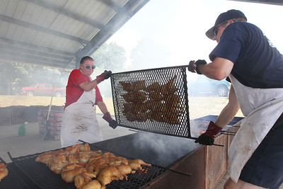 Candace H. Johnson-For Shaw Media Antioch firefighters Marianne Peistrup and her husband, Tim, turn the chicken on the grill during the Antioch Lions Club Chicken BBQ, Pig Roast & Auction at Williams Park in Antioch.(7/29/18)