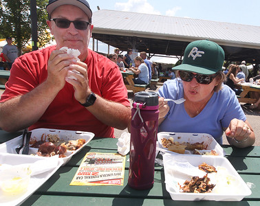 Candace H. Johnson-For Shaw Media Jim and Mary Zaino, of River Forest enjoy eating their chicken and pork BBQ dinners during the Antioch Lions Club Chicken BBQ, Pig Roast & Auction at Williams Park in Antioch.(7/29/18)