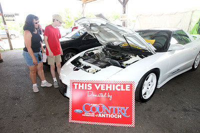 Candace H. Johnson-For Shaw Media Pam Makis, of Antioch and her son, Zachary, 15, check out a car donated by Kunes Country Stateline Superstore of Antioch for the auction during the Antioch Lions Club Chicken BBQ, Pig Roast & Auction at Williams Park in Antioch.(7/29/18)