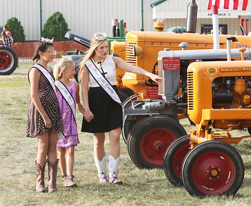 Candace H. Johnson-For Shaw Media Lily Troyan, 13, Jenna Marasco, 8, and Teaghan Callaway, 19, all of Lake Villa, newly crowned Lake County Fair queens, look at tractors as they walk through the Lake County Farm Heritage display during the Lake County Fair at the Lake County Fairgrounds in Grayslake. (7/25/18)