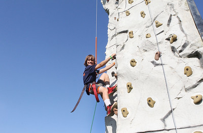 Candace H. Johnson-For Shaw Media Ehren Curry, 10, of Evanston is all smiles as he makes his way up the climbing wall during the Taste of Grayslake Family Picnic & Fireworks in Central Park in Grayslake. (6/29/19)