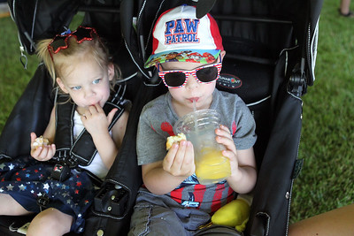 Candace H. Johnson-For Shaw Media Adelynn Tobie, 2, of Antioch and her brother, Lincoln, 3, enjoy a funnel cake and lemonade in their stroller during the Taste of Grayslake Family Picnic & Fireworks in Central Park in Grayslake. (6/29/19)