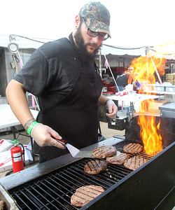 Candace H. Johnson-For Shaw Media Tony Vazquez, of Island Lake, general manager of Bulldogs Grill, cooks some hamburgers on the grill for customers during Wauconda Fest at Cook Park in Wauconda. (6/29/19)