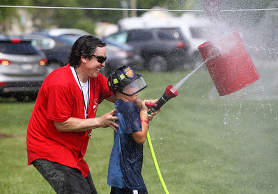 Candace H. Johnson-For Shaw Media Battalion Chief Devin Mueller helps Charlie Buschick, 9, of Wauconda compete in the Wauconda Fire Department's Kids Water Fights during Wauconda Fest at Cook Park in Wauconda. (6/29/19)