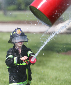 Candace H. Johnson-For Shaw Media Eli Pedraza, 4, of Wauconda pushes the barrel with a water hose as he competes in the Wauconda Fire Department's Kids Water Fights during Wauconda Fest at Cook Park in Wauconda. (6/29/19)