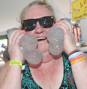 Candace H. Johnson-For Shaw Media Donna Gruhlke, of Wauconda cools off with some cold water bottles on a hot day during Wauconda Fest at Cook Park. (6/29/19)