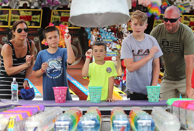 Candace H. Johnson-For Shaw Media Lisa Buschick, of Wauconda watches her sons, Charlie, 9, and Colin, 6, play the hermit crab/goldfish game with Christian Leisten, 11, of Lakemoor and his father, Scott, during Wauconda Fest at Cook Park in Wauconda. (6/29/19)