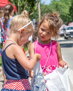 Vada Barchard (age 4) (left) and Hazel Cox (age 4) compare candy during the Crystal Lake Independence Day parade Sunday, July 7, 2019 on Dole Avenue in Crystal Lake.  KKoontz - For Shaw Media