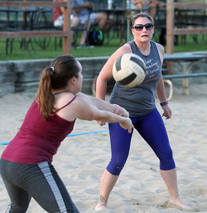 "Candace H. Johnson-For Shaw Media Stephanie Carlson passes the ball as she stands close to Kim Mersch, both of McHenry with the Intermediate 6's team called, ""Calm Your Tips,"" as they play against ""I'd Hit That,"" during a Sideouts Beach Volleyball League Tuesday night game in Island Lake. (7/9/19)"