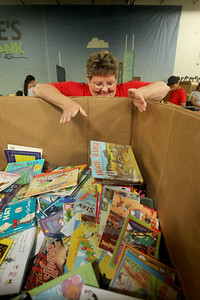 Candace H. Johnson-For Shaw Media Donna Baseley, of McHenry drops sorted books by grade into a large bin to be bagged and distributed to students during the 10th Anniversary Celebration & Volunteer-A-Thon at Bernie's Book Bank in Lake Bluff. (7/13/19)