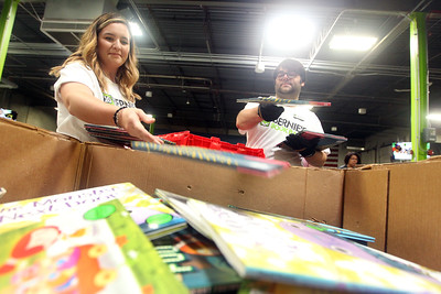 Candace H. Johnson-For Shaw Media Lauren Marquez, of Gurnee, processing center specialist, and Bill Nixon, of Lake Zurich, volunteer experience manager, sort preschool and first grade books and put them into large bins during the 10th Anniversary Celebration & Volunteer-A-Thon at Bernie's Book Bank in Lake Bluff. (7/13/19)