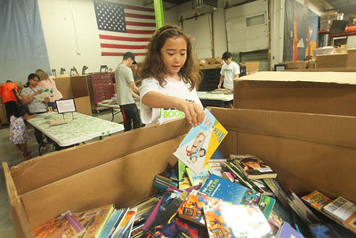 Candace H. Johnson-For Shaw Media Jasmyne Brody, 7, of Deerfield drops a book into a large bin during the 10th Anniversary Celebration & Volunteer-A-Thon at Bernie's Book Bank in Lake Bluff. (7/13/19)
