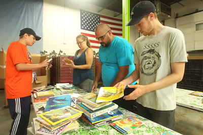 Candace H. Johnson-For Shaw Media Carmine Virginelli, 13, of Kildeer sorts books with members of his family, Sandra and Dan Schafer and Sandra's son Cage Murawski, 22, all of Wauconda during the 10th Anniversary Celebration & Volunteer-A-Thon at Bernie's Book Bank in Lake Bluff. (7/13/19)